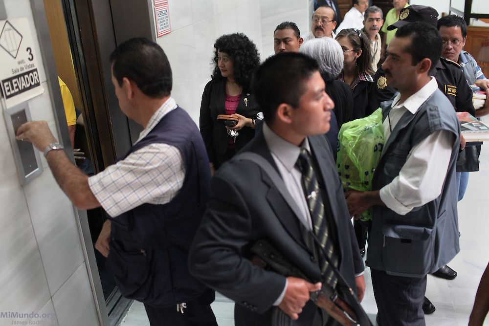 An armed security guard watches as Judge Jazmin Barrios enters an elevator for deliberations. For the first time in world history, a former head of state was not only tried for genocide and crimes against humanity in a national court, but found guilty of these charges. Former Guatemalan de facto head of state Jose Efrain Rios Montt, who ruled Guatemala from March 1982 to August 1983, was sentenced to 80 years of jail. Guatemala City, Guatemala. May 10, 2013.