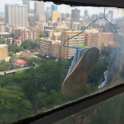 Shoes hung out of a window to dry in Highrise, a 19-storey apartment tower overlooking a park and downtown in Hillbrow, an inner-city neighbourhood in Johannesburg, South Africa. Once the exclusive domain of wealthy white South Africans during the apartheid era, today the building has a reputation for being the residence of choice for drug dealers who operate in the park across the street.