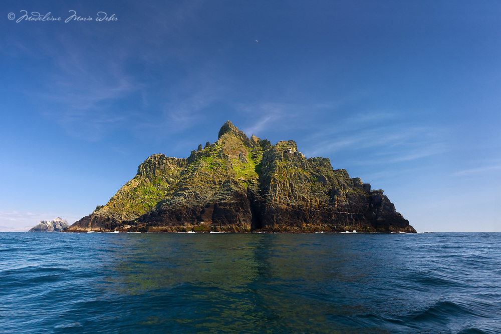 Skellig Michael from the sea with the Old Lighthouse and the South Peak and a clear blue sky day with a reflexion on the calm Atlantic sea, County Kerry, Skellig Coast, Skellig Ring, Ireland.<br /> <br /> DEUTSCH: Skellig Michael, der alte Leuchtturm und die Sued Spitze and einem Blauen-Himmel-Tag.<br /> <br /> ****** <br /> <br /> Visit &amp; browse through my Photography &amp; Art Gallery, located on the Wild Atlantic Way &amp; Skellig Ring between Waterville and Ballinskelligs (Skellig Coast R567), only 3 minutes from the main Ring of Kerry road.<br /> https://goo.gl/maps/syg6bd3KQtw<br /> <br /> ******<br /> <br /> Contact: 085 7803273 from an Irish mobile phone or +353 85 7803273 from an international mobile phone