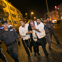 Under covered Israeli police officers, dressed as ultra orthodox, arrest an ultra orthodox protestor during riots in Mea shearim neighborhood in Jerusalem.