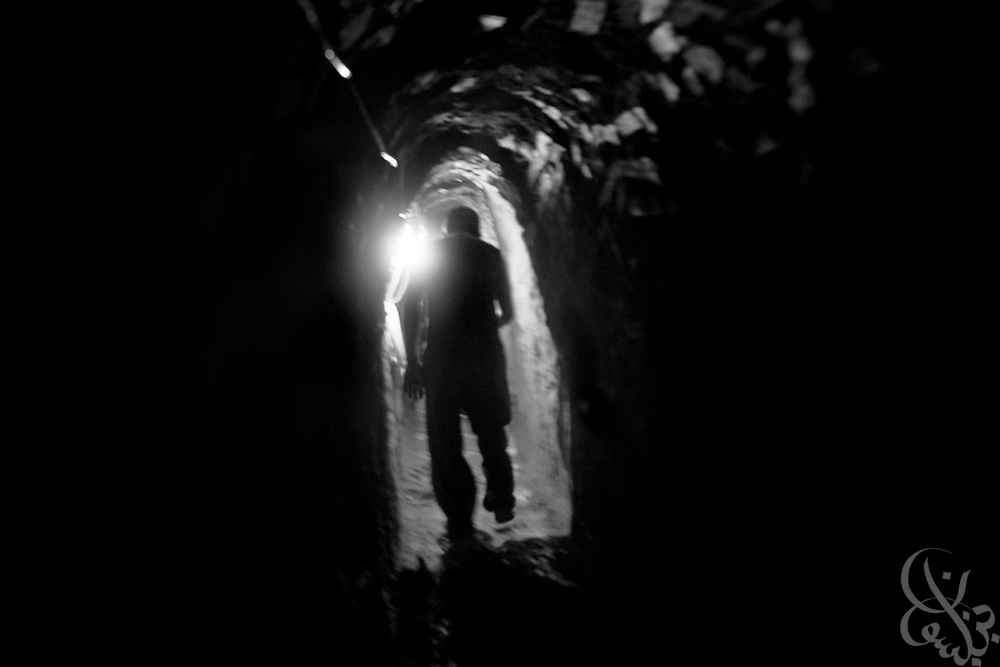 A Palestinian worker moves through a damaged smuggling tunnel on the Gaza-Egypt border in Rafah, Gaza January 22, 2009. Since the end of the 22 day Israeli military operation that included heavy airstrikes on the tunnel area, Palestinians have been busy reopening the undamaged tunnels, and rebuilding more heavily damaged or destroyed ones.  ..