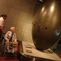 Tsutomu Yamaguchi ( in wheelchair) helped by his son-in-law, visits a replica in Nagasaki Atomic Bomb Museum, of the 'Fat Man' atomic bomb dropped on Nagasaki on 9th August 1945, at 11.02am. In the Nagasaki Atomic bomb museum on Tuesday May 24th 2005. Yamaguchi was in Hiroshima on the day of the first atomic bombing, 6th Aug. 1945, and also in Nagasaki three days later on the day of the second atomic bombing of Japan by US Military. Nagasaki, Japan.