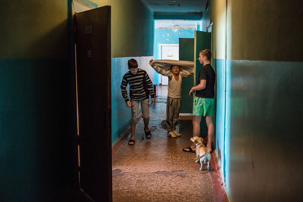 DNIPRODZERZHINSK, UKRAINE - OCTOBER 11: Vladyk, Oleg, and Yegor (L-R), play in a hallway at the sports school where they live with about 60 other displaced people from Eastern Ukraine on October 11, 2014 in Dniprodzerzhinsk, Ukraine. The United Nations has registered more than 360,000 people who have been forced to leave their homes due to fighting in the East, though the true number is believed to be much higher.(Photo by Brendan Hoffman/Getty Images) *** Local Caption ***