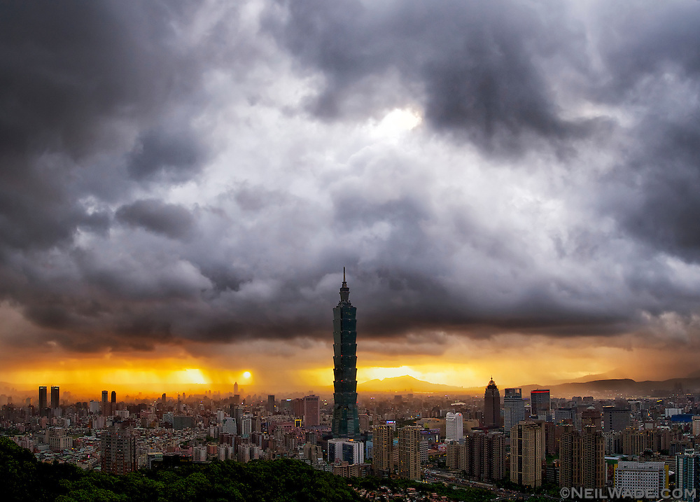 Evening settles over Taipei City and Taipei 101 and a typhoon approaches northern Taiwan.