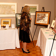 Charles Taylor, who retired last year as dean of the WSU College of Liberal Arts (left) looks at silent auction items during the 14th Annual ArtsGala at Wright State University's Creative Arts Center, Saturday, April 6, 2013.