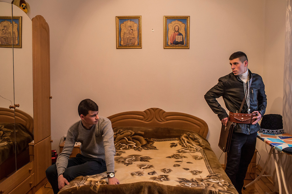 Mykola Danko, 18, left, watches as Ivan Istratii, 20, right, tries on the outfit he will wear as commandant of the Trazhan district for the Malanka Festival on Wednesday, January 13, 2016 in Krasnoilsk, Ukraine. The commandant is responsible for coordinating the roving group of revelers in his district. The festival will begin at sundown and last until the following evening.