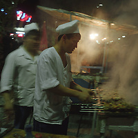 Restaurant owner cooks Shishlik kebabs on an outdoor fire in the nightly street market in Tashkent, one of the cities of the old Silk Road trading route. Uzbekistan.