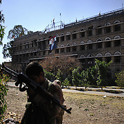An defected soldier stands in front of the burnt-out GPC building (the headquarters of President Ali Abdullah Saleh's party) in the neighbourhood of Hasaba in Sana'a on 05 December 2011.