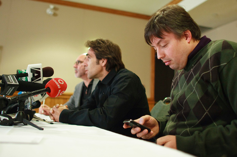 Sam Sansalone, right, a representative of the family of baby Joseph Maraachli uses his blackberry as Bobby Schindler, centre, brother of Terri Schiavo and the executive director of the Terri Schiavo Life and Hope Network speaks to the media during a press conference in London Ontario, Thursday, February 24, 2011. Baby Joseph's family has been in a fight with the London Health Sciences Centre over the removal of life support.<br /> THE CANADIAN PRESS/ Geoff Robins