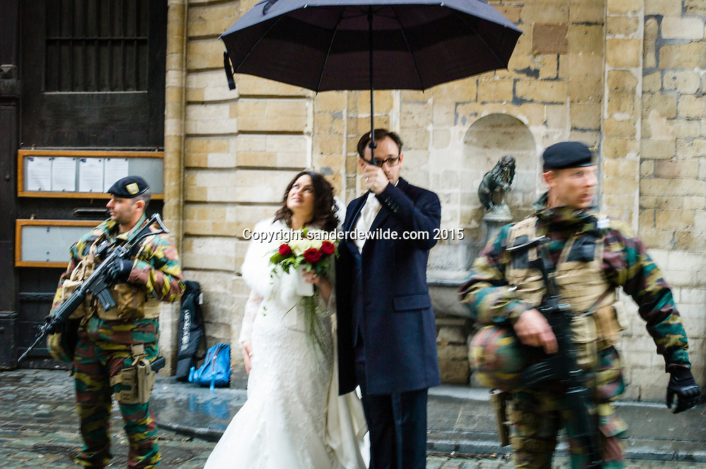 """Brussels Belgium 21 November 2015. Terror alert level for Brussels was put at 4, the maximum on a scale of 1 to 4. There is """"a very concrete and imminent threat"""".These Greek-Flemish newly weds got married and have a portrait made with the military posing for their special marriage day. Bride Konstantina Karadimitropoulou and groom Roeland Lacroix holding umbrella"""