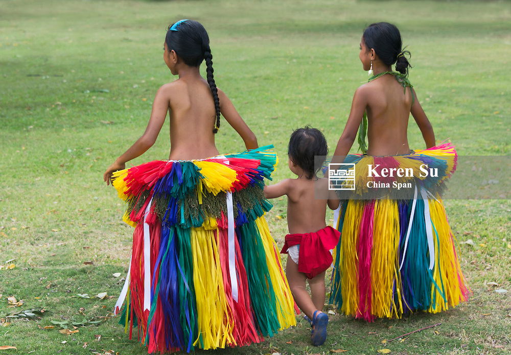 Yapese girls wearing grass skirt with a little boy at Yap Day Festival, Yap Island, Federated States of Micronesia