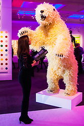 """London, March 4th 2015. Sotheby's in London hosts """"one of the most extraordinary collections of our time"""", an anonymous collector's vast assembly of fine art pieces, including skulls, bear sculptures, paintings and installations. PICTURED: A woman examines Paola Pivi's """"Life Is Great"""", a giant polar bear sculpture covered in feathers."""