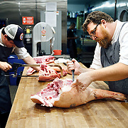 SHOT 8/14/13 6:09:17 PM - Justin Brunson (right), Owner and Executive Chef at Old Major butchers half a hog with Sous Chef Spencer Whitaker into specific cuts at the restaurant in Denver, Co. The pigs are raised locally in Brush, Co. and Brunson buys two a week that he then butchers in-house and uses the entire hog in various dishes in the restaurant. The restaurant focuses on heritage-raised meats from Colorado farms, features an in-house butchery program and bills itself as contemporary farmhouse cuisine. (Photo by Marc Piscotty / © 2013)
