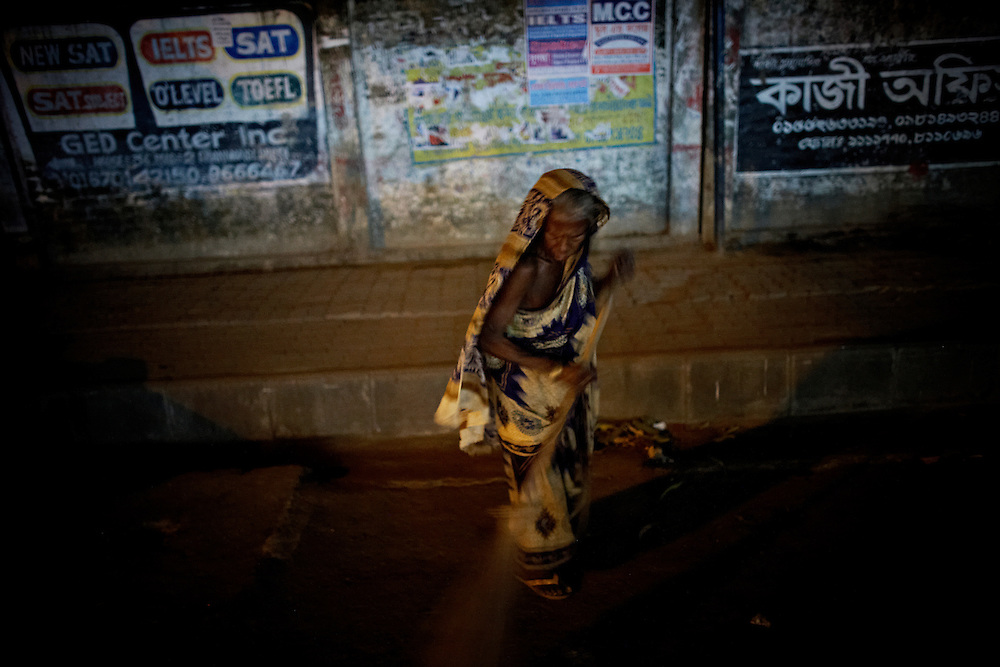 A woman sweeping the road, Dhaka Bangladesh...Bangladesh is a country of 150 million people where 80% live for less than a dollar a day, making it one of the poorest countries in the world. thousands live on the streets, trying to make the best of the little they have...Bangladesh has finished with two years of emergency rule. The election results is compared to the landslide of 1970 that led to war and independence from Pakistan. .When preparations for the election started in late 2006, violent street-protests started, and led to a military backed interim government until the election happened under heavy security and watchful eyes on December 29th 2008...The past two years have seen a decrease of crime and corruption but also sparked violent student protests and curfews. Today  most people seem to be happy to return to some sort of normality. But in one of the poorest countries in the world where 80% live for less than a dollar a day, does it really matter who is in power? The circus is over, back to reality and putting food on the table...A blogger  from dhaka is quoted Ó we prefer messy democracy to military ruleÓ...Is this the end of night, a new dawn or yet another dusk?..Photo by: Eivind H. Natvig/MOMENT *** Local Caption ***