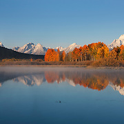 Many of the prominent peaks in Grand Teton National Park, Wyoming, are reflected in the water of Oxbow Bend on an autumn morning. The major peaks, from left to right, are Grand Teton, Rockchuck Peak, Mount Woodring, and Mount Moran.