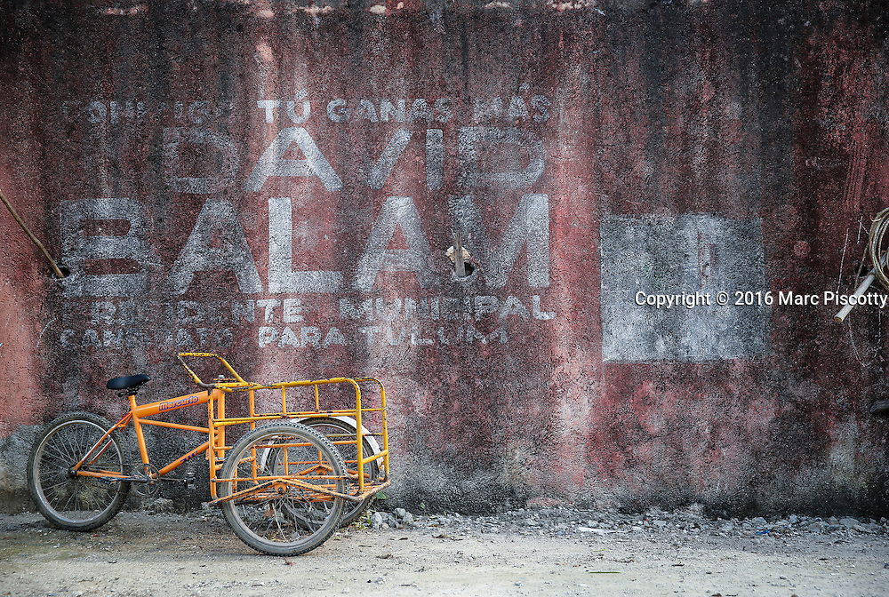 SHOT 12/9/16 2:03:01 PM - A three wheeled work/transport bicycle sits idle beside a wall in Macario Gomez just outside of Tulum, Mexico. Tulum is located in the Mayan Riviera and along the east coast of the Yucatán Peninsula on the Caribbean Sea in the state of Quintana Roo, Mexico. (Photo by Marc Piscotty / © 2016)