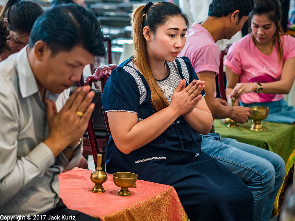 """14 FEBRUARY 2017 - BANGKOK, THAILAND: A couple prays while their wedding is blessed in the Bang Rak district in Bangkok. Bang Rak is a popular neighborhood for weddings in Bangkok because it translates as """"Village of Love."""" (Bang translates as village, Rak translates as love.) Hundreds of couples get married in the district on Valentine's Day, which, despite its Catholic origins, is widely celebrated in Thailand.      PHOTO BY JACK KURTZ"""