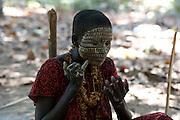 Etalé se maquille. Elle porte une robe rouge, la couleur préférée des Jarawas. Les habits, mais aussi son petit miroir, sont troqués contre du miel ou du gibier avec les braconniers et les gardes forestiers indiens.