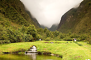 Ecuador. Hacienda Zuleta in the Andes Mountain Range.  Waterfall  into a small pond and mist on the mountain peaks beyond.