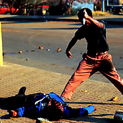 POLITICS CONFLICT SOUTH AFRICA 15SEP90 - A man stabs at Lindsay Tshabalala, a Zulu killed as a suspected Inkatha member by African National Congress supporters.  Over 3,000 people died in 1990 as a result of ANC-Inkatha violence that was provoked by a state-sponsored destabilisation programme, prior to South Africa's first democratic elections in 1994.  (Photo by Greg Marinovich )