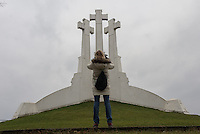 A tourist makes a photograph of the Hill of Three Crosses in Vilnius, Lithuania. The crosses were erected on a hill in Vilnius to commemorate a group of monks from a nearby monastery who were martyred in the 14th century. This current cross was built in 1989 at the beginning of the rebirth movement, replacing one removed by the Soviets in the 1950's.