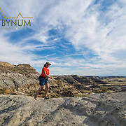hiker on ridge in prairie badlands painted clifs