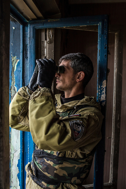 Pro-Russian rebel commander Mikhail Sergeevich Tolstikh, known as Givi, looks through binoculars in an apartment building where his forces can observe and coordinate fighting to gain control of the Donetsk airport on Friday, October 17, 2014 in Donetsk, Ukraine. Photo by Brendan Hoffman, Freelance