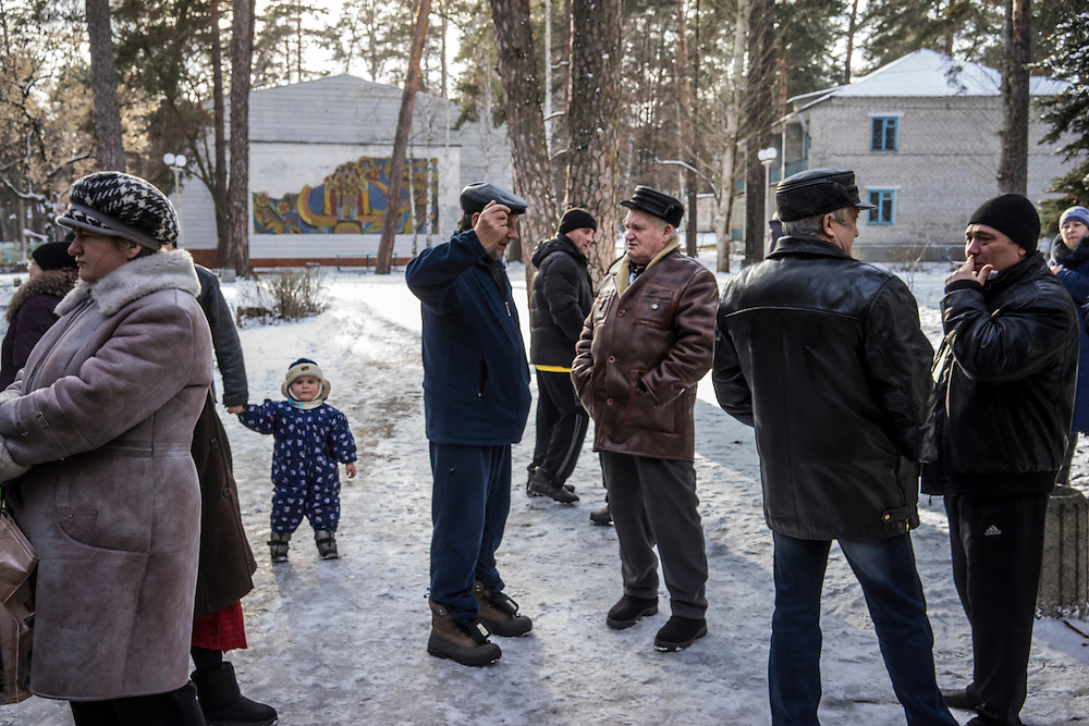 People who fled fighting between pro-Russia rebels and Ukrainian forces gather outside the canteen at the Perlyna Donetchyny children's resort, where they are temporarily seeking refuge, on Monday, February 9, 2015 in Svyatogorsk, Ukraine.