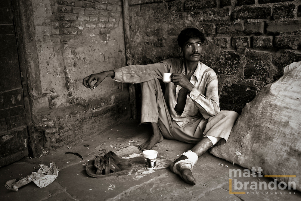 A homeless man drinks tea in an alleyway of old Delhi next to his bag of recycled aluminum.