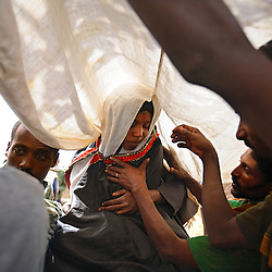 In the Amhara Region, family members place a white cloth over the head of Leyualem, 14, as her new groom and groomsmen prepare to whisk her away on a mule. Leyualem had never met her husband before her wedding day, yet submitted as they bound her in the white wedding cloth. The men later said it was placed over her head so she would not be able to find her way back home, should she want to escape the marriage.
