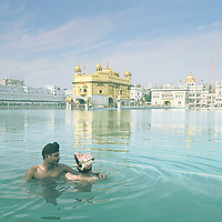 Two young men bathe in the Sarovar, the sacred waters surrounding the Golden Temple in Amritsar, Punjab, India.<br /> <br /> Also known as Swarna Mandir, the Temple's roof is plated with pure gold. Live shabad is sang (verses of the 'Holy Text') and broadcast throughout the complex.