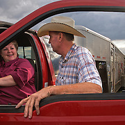 Steve Taylor chats with Catherine Bay, owner of the Bar B ranch near Albia, Iowa, during a bi-annual cattle roundup in August of 2008.  Bay hires a crew of local cowboys to herd calves for vaccinations, branding and the placement of growth stimulant implants.  The male calves were also castrated.   Bay owns a herd of over 2,000 cattle.  Taylor, a local farmer, provides feed for Bay's herd.