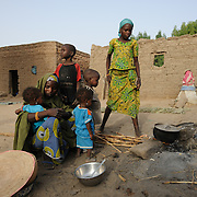 Adama Garba with five of her six children as she prepares the evening meal at their home in the village of Nakaidabo in the Tessaoua region of Niger. This evening she has only a few handfuls of beans and a pinch of salt for her family of seven.