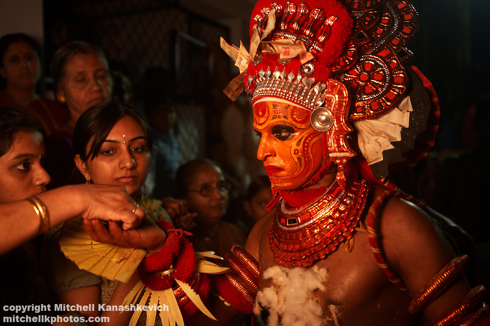 Devotees donate money to a Theyyam performer in Kannur District, Kerala, India. .It is believed that while performing; the artist is possessed by a divine spirit and becomes a God - or Theyyam in the local language. In Hinduism there are literally millions of Gods; both good and evil and the four hundred existing variations of Theyyam performances are dedicated to just some of them.