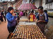 31 JULY 2015 - KATHMANDU, NEPAL:  A woman prays over butter lamps during the full moon processions at Bodhnath Stupa. Bodhnath Stupa in the Bouda section of Kathmandu is one of the most revered and oldest Buddhist stupas in Nepal. The area has emerged as the center of the Tibetan refugee community in Kathmandu. On full moon nights thousands of Nepali and Tibetan Buddhists come to the stupa and participate in processions around the stupa. The stupa was heavily damaged in the earthquake of 25 April 2015 and people are no longer allowed to climb on the stupa, now they walk around the base and pray with butter lamps.  PHOTO BY JACK KURTZ