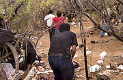 A group of about twenty illegal immigrants, who crossed into the U.S. from Mexico on to the Tohono O'odham Nation, moves through a staging area during the midday heat east of Sells at Little Tucson, Arizona, USA.  The group moved without the presence of the Border Patrol or other law enforcement agency.