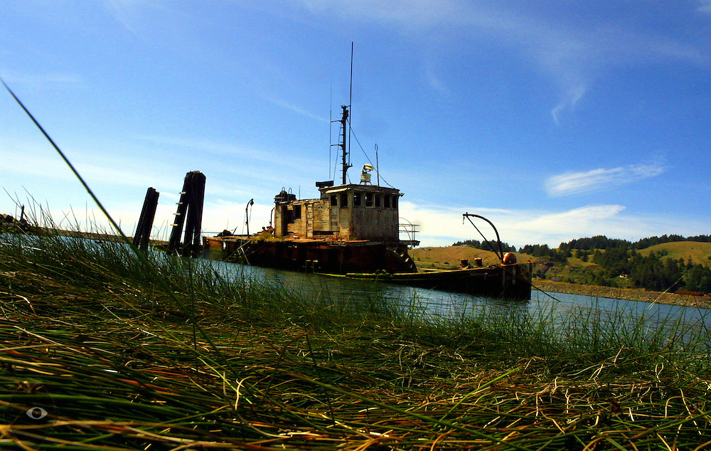 An old boat spends the last of its life mired in a canal amongst low water and reeds off the Oregon coast.