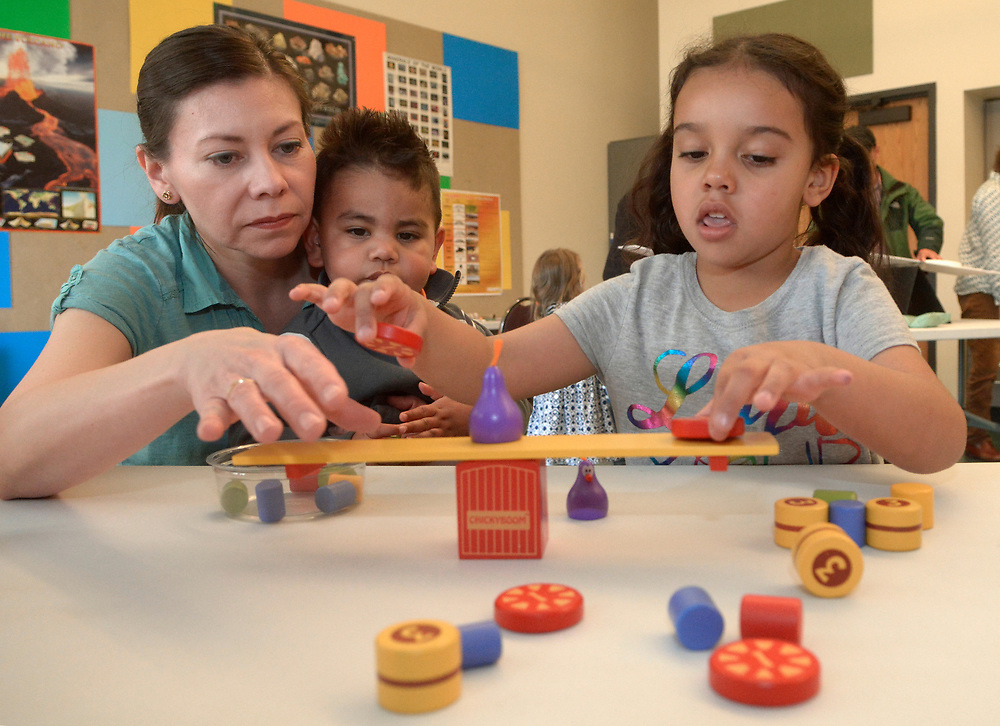 """gbs030517i/ASEC -- Elizabeth Espinosa of Bosque Farms with her son, Issac, 2, and niece, Olivia Otero, 4 , of Rio Ranchoexperiment with balancing weights during a Family Science Workshop at the New Mexico Museum of Natural History and Science on Sunday, March 5, 2017. The """"Balancing Act"""" workshop lets kids and parents explore and manipulate the placement of weights and balancing their own bodies. The next Family Science Workshop """"The Force Is With You"""" is on April 2, 2017.(Greg Sorber/Albuquerque Journal)"""