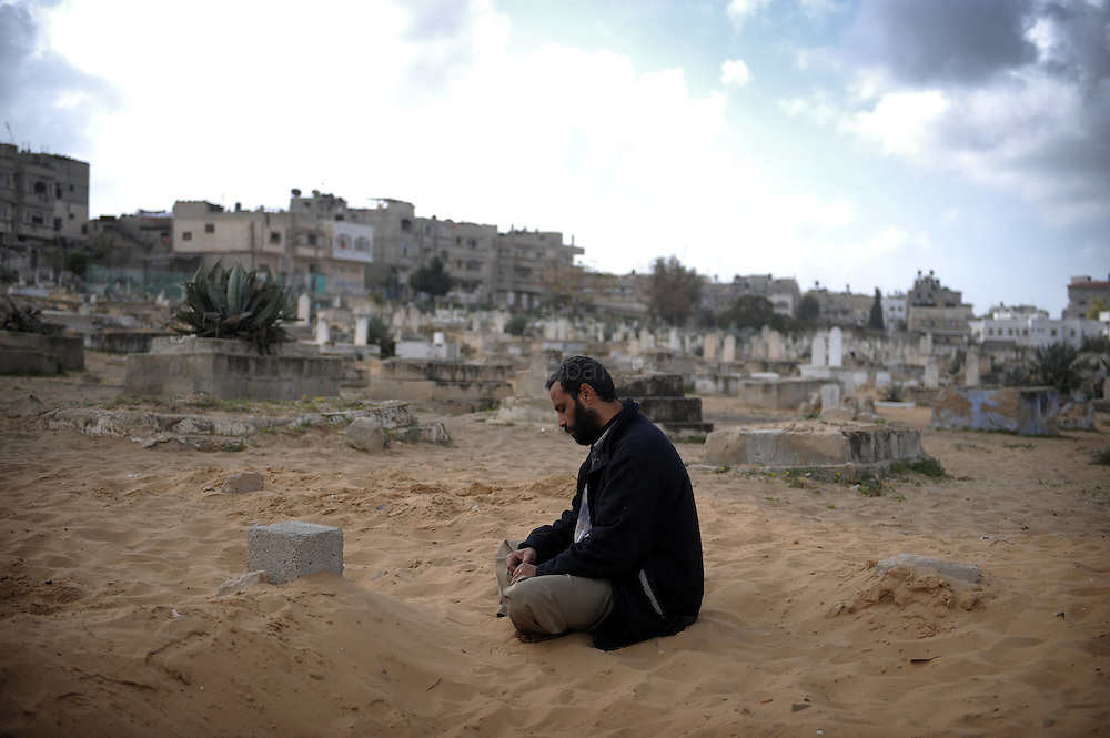 A Palestinian man prays on the tomb of a relative killed during Israel's 22-day military operation over Gaza, at a cemetery in Gaza City on January 29, 2009. US envoy George Mitchell called for a durable truce in Gaza as spiralling violence threatened to shatter ceasefires that ended a devastating war in the Hamas-run enclave.