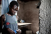 Winner, Photo District News FACES 2011 portfolio. A disabled girl looks despondent as she opens a bag of crackers in a camp in Port au Prince