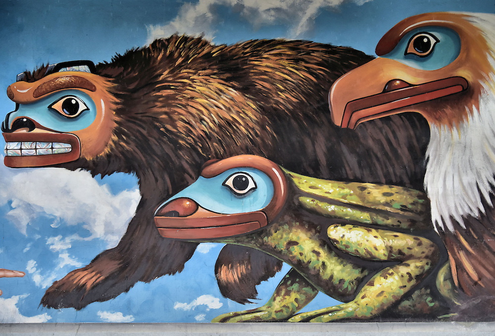 City Hall Mural by Bill Ray in Juneau, Alaska <br /> This brown bear, lizard and eagle with totem-pole style faces are part of a mural by Bill Ray on the side of Juneau&rsquo;s City Hall on Marine Way.  Off camera they are staring at a male member of the Tlingit clan with a raven on his back.  The Tlingits are indigenous people of the Pacific Northwest Coast.  Their societies are descendants of either the Raven or the Eagle.  This art depicts their story of creation.
