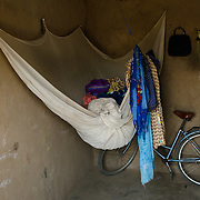 A mosquito net is used to store clothes in the room Rihanata Ouedraogo shares with her mother, Zalissa Rabo, in Koala, Bukina Faso on 27 February 2014. Many people only sleep under their nets during the rainy season, when mosquitoes (and malaria) are most prevalent.