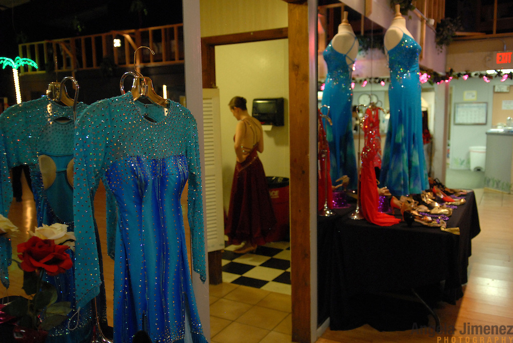 Same-sex ballroom dancer Citabria Phillips, center, of Oakland, California, gets dressed in the women's restroom before competing in the USADSF (United States Alternative Dancesport Federation) Same-Sex Ballroom Championships at Dance Orlando in Orlando, Florida on June 2, 2007...The clothes in the foreground are a display by The Dance Dresser ballroom costume company. ..Nine male and female couples from around the country competed in the event, which was the 3rd annual United States championship contested in this sport: the first two championships were held in Sacramento, California in 2005 and 2006. This was the first same-sex ballroom competition ever held in Florida. ..Same-sex ballroom dancing is a new sport which is growing and developing in the United States, but it has a longer history in Europe, where events have been held for over two decades.  ..