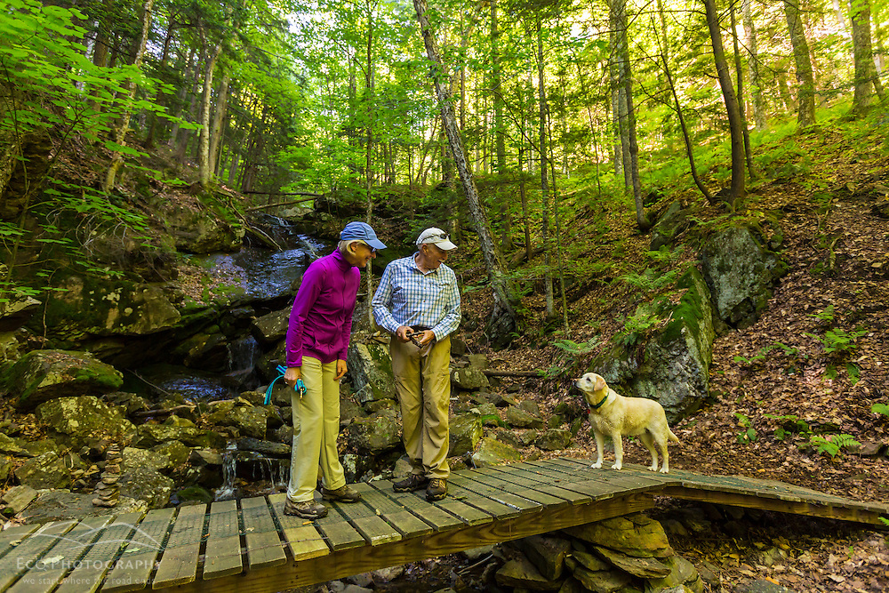 A couple stands on a bridge with their yellow lab on a trail on Mount Ascutney in West Windsor, Vermont.