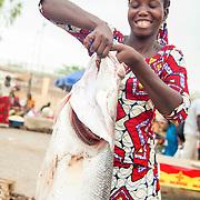 LÉGENDE: Une vendeuse, sourire aux lèvres montre fierèment le gros poissons capitaine. LIEU: Marché de Chagoua, N'Djaména, Tchad. PERSONNE(S): Une vendeuse de poissons (au centre de la photo).