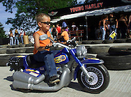 A youngster rides a battery-powered toy motorcycle at the Harley-Davidson Experience in downtown Milwaukee August 30, 2003. The legendary American motorcycle company is celebrating its 100th anniversary over four days.    REUTERS/Rick Wilking