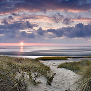 The sun emerged from behind the clouds just prior to setting at First Encounter Beach in Eastham
