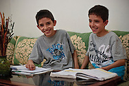 Anass and his twin brother at home chatting with each other while looking into notes of the afternoon classes.