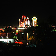 A ferris wheel and another ride of a nearby Fair light up the dark night sky in Lake Havasu City, Arizona.