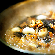 "SHOT 2/17/12 7:12:40 PM - Mushrooms and cippolini onions simmering in a prep pan at TAG restaurant on Larimer Square in downtown Denver, Co. Both restaurants are operated by chef/owner Troy Guard. TAG features what they term ""continental social food"" and features influences from numerous continents. (Photo by Marc Piscotty / © 2012)"
